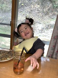 窓の前のテーブルに座っている赤ちゃんの写真・画像素材[2797085]