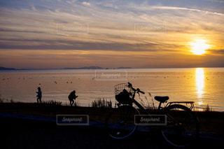 夕日の沈む水辺で遊ぶ女の子2人と自転車のシルエットの写真・画像素材[2853760]