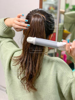 ヘアアイロンで髪型を整える女性の写真・画像素材[2888311]