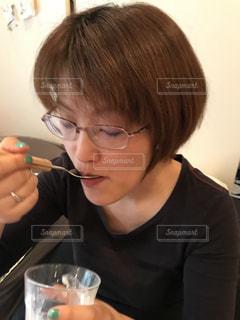 ワイングラスを持つテーブルに座っている女性の写真・画像素材[1150192]