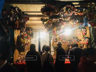 クリスマスツリーのある暗い部屋の人々のグループの写真・画像素材[2840382]