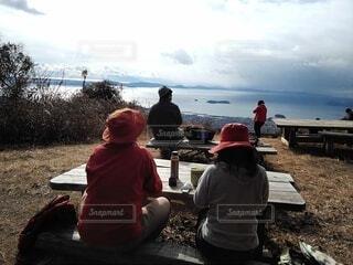 山の頂上のベンチ座って海を見る人たちの写真・画像素材[4026469]