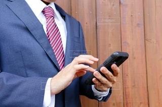 スーツを着た男性がスマホを触るの写真・画像素材[3545209]
