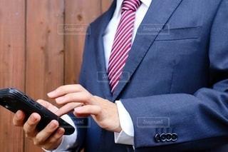 スーツを着た男性がスマートフォンを触るの写真・画像素材[3545213]