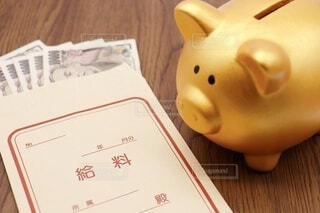 豚の貯金箱と給料袋の写真・画像素材[3898247]