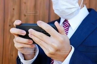 スーツとマスクを着用した日本人男性がスマートフォンを見ているの写真・画像素材[3932393]