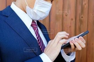 スーツとマスクを着用した日本人男性がスマートフォンを見ているの写真・画像素材[3932395]