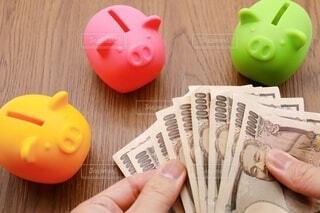 3色の豚の貯金箱と一万円札の写真・画像素材[3966593]