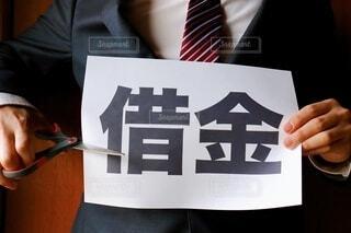 借金と書かれた紙とビジネスマンの写真・画像素材[4202989]