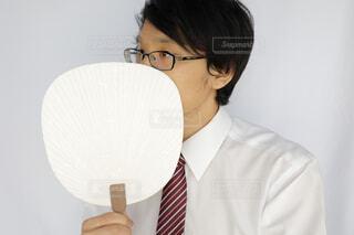 うちわで口を覆うスーツの男性の写真・画像素材[4326318]
