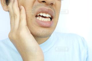 頬を押さえる男性の写真・画像素材[4441778]