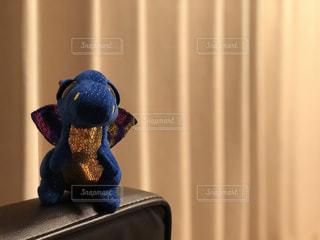 ソファーの角っこに座る恐竜のぬいぐるみの写真・画像素材[2211368]