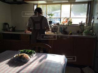 窓の前のテーブルに座っている人の写真・画像素材[2858774]