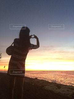 夕日の前に立っている人の写真・画像素材[3313112]