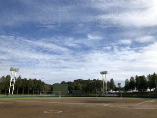 青空と雲の下にある緑の多い野球場の写真・画像素材[3224949]