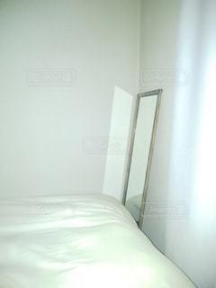 部屋の白いベッドと鏡の写真・画像素材[2892504]