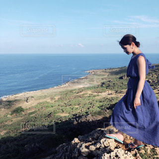 岩の多い浜辺に立っている女の写真・画像素材[2867833]
