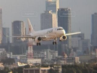 都市の上空を飛ぶ飛行機の写真・画像素材[2874440]
