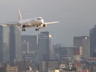 都市の上空を飛ぶ大型旅客機の写真・画像素材[2874940]