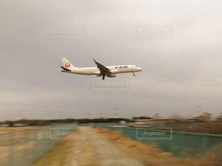曇った空を飛んでいる大きな旅客機の写真・画像素材[2892395]