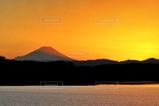 山を背景にした水域に沈む夕日の写真・画像素材[2929809]