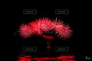 夜空に浮かび上がる真っ赤な花火の写真・画像素材[4708313]