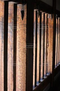 フェンスの隣に座っている木製のベンチの写真・画像素材[2975799]
