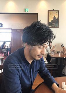 テーブルの上に座っている男性の写真・画像素材[2932031]