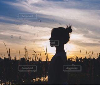 背景に夕日がある人の写真・画像素材[2921821]