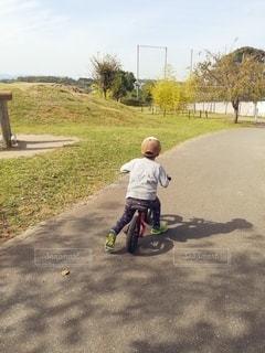 自転車に乗って未舗装の道路を下る少年の写真・画像素材[2970764]