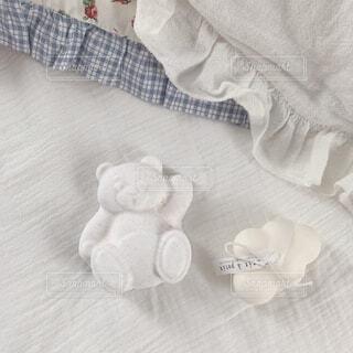 ベッドの上に置いたバスボムとろうそくの写真・画像素材[3975030]