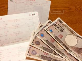 木製のテーブルの上の紙幣の写真・画像素材[3008878]