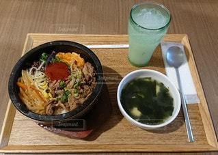 木製のテーブルの上に座っている食べ物のボウルの写真・画像素材[3295336]