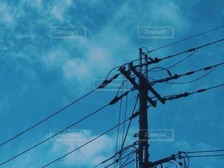 電線と電柱越しの空の写真・画像素材[2935409]