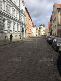 建物の側面に車が止まっている狭い街の通りの写真・画像素材[2939580]