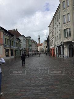 レンガの建物の隣の通りを歩いている人々のグループの写真・画像素材[2939549]