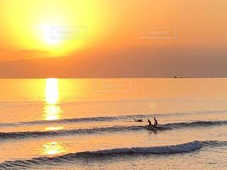 サーファーと大きな夕陽の写真・画像素材[2968192]