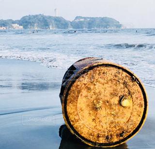 大きなドラム缶を拾って届けた夏のビーチの写真・画像素材[2968364]