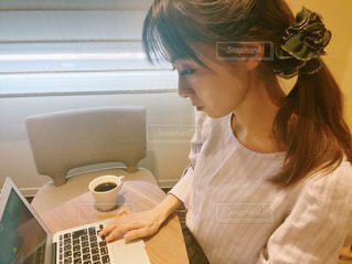 ラップトップを使ってテーブルに座っている女性の写真・画像素材[3204633]