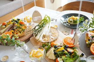 食べ物の皿をテーブルの上に置くの写真・画像素材[3014985]