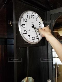 時計の隣に立っている人の写真・画像素材[2988129]