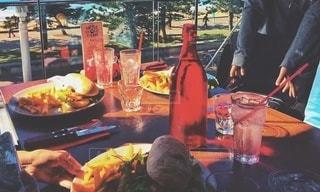 食べ物を持ってテーブルに座っている人の写真・画像素材[2988886]