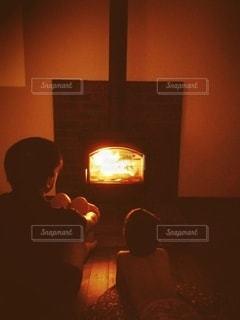 薪ストーブで暖をとる親子の写真・画像素材[2990412]