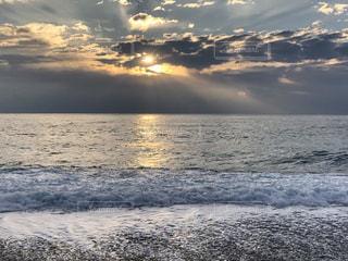 海の隣のビーチに沈む夕日の写真・画像素材[2993808]