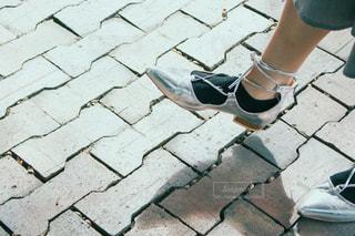 歩道に立っている青と白の靴を履いた足のクローズアップの写真・画像素材[3020872]
