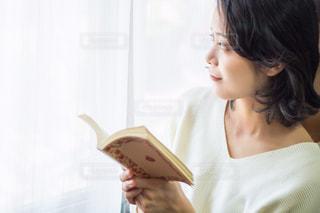 窓際で本を読む女性の写真・画像素材[3151489]