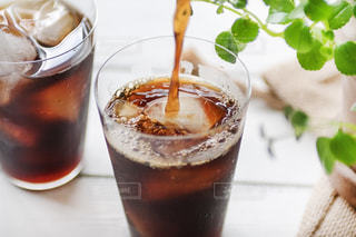 白いテーブルの上のアイスコーヒーと観葉植物の写真・画像素材[3036072]