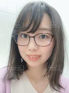 眼鏡をかけてカメラに向かって微笑む女性の写真・画像素材[3038088]