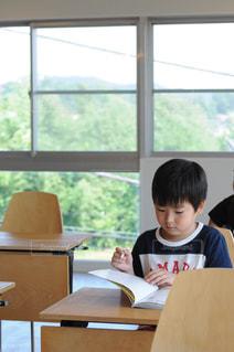 窓の前のテーブルに座っている少年の写真・画像素材[794931]
