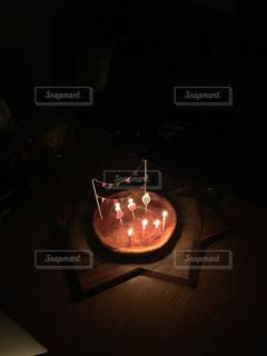 テーブルの上に座ってロウソクでケーキの写真・画像素材[1468082]